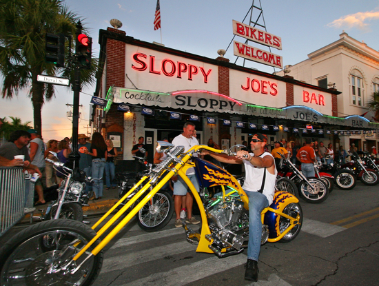 In this photo released by the Florida Keys News Bureau, a motorcycle enthusiast parks his bike in front of Sloppy Joe's Bar in Key West, Fla., during the 35th Annual Key West Poker Run Friday, Sept. 14, 2007. Riders on as many as 10,000 bikes have traversed down the Florida Keys Overseas Highway, drawing cards at designated stops. The weekend event, that ends Sunday, serves as a charity fundraiser for the Diabetes Research Institute and educational scholarships for Keys students. (AP Photo/Florida Keys News Bureau, Rob O'Neal)