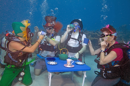 "Divers including from left, Katie Jennele, Bob Rowland, Eric Rolfe and Alicia Merel act out an ""Alice in Wonderland"" underwater tea party at the Underwater Music Festival in the Florida Keys National Marine Sanctuary Saturday, July 10, 2010, near Big Pine Key, Fla. The annual subsea concert attracted more than 500 divers and snorkelers to listen to a local radio station's broadcast piped beneath the sea with underwater speakers. (Bob Care/Florida Keys News Bureau)"